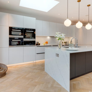 Photo of a contemporary l-shaped kitchen in London with a submerged sink, flat-panel cabinets, white cabinets, white splashback, stone slab splashback, stainless steel appliances, light hardwood flooring, an island, beige floors and white worktops.