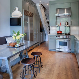 This is an example of a medium sized victorian l-shaped enclosed kitchen in Toronto with granite worktops, a double-bowl sink, shaker cabinets, green cabinets, white splashback, porcelain splashback, stainless steel appliances, light hardwood flooring and no island.