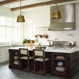 ヒューストンの中サイズのトランジショナルスタイルのおしゃれなキッチン (エプロンフロントシンク、落し込みパネル扉のキャビネット、白いキャビネット、シルバーの調理設備の、珪岩カウンター、白いキッチンパネル、レンガのキッチンパネル、磁器タイルの床、グレーの床) の写真