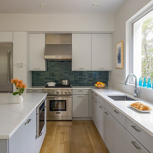 Mid-sized modern open concept kitchen designs - Mid-sized minimalist l-shaped open concept kitchen photo in Boston with flat-panel cabinets, gray cabinets, quartz countertops, white backsplash, stainless steel appliances and an island