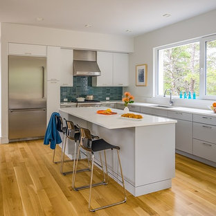 Mid-sized minimalist l-shaped light wood floor open concept kitchen photo in Boston with an undermount sink, flat-panel cabinets, gray cabinets, quartz countertops, white backsplash, stainless steel appliances and an island