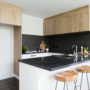 Small contemporary u-shaped open plan kitchen in Other with a drop-in sink, white cabinets, laminate benchtops, black splashback, ceramic splashback, black appliances, vinyl floors, no island, brown floor and black benchtop.
