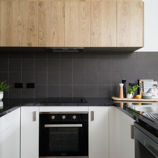Inspiration for a small modern u-shaped open plan kitchen in Other with a drop-in sink, white cabinets, laminate benchtops, black splashback, ceramic splashback, black appliances, vinyl floors, no island, brown floor and black benchtop.