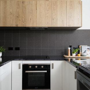 Offene, Kleine Moderne Küche ohne Insel in U-Form mit Einbauwaschbecken, weißen Schränken, Laminat-Arbeitsplatte, Küchenrückwand in Schwarz, Rückwand aus Keramikfliesen, schwarzen Elektrogeräten, Vinylboden, braunem Boden und schwarzer Arbeitsplatte in Sonstige