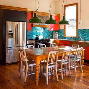This is an example of an eclectic l-shaped kitchen/diner in Auckland with flat-panel cabinets, red cabinets, mosaic tiled splashback and stainless steel appliances.