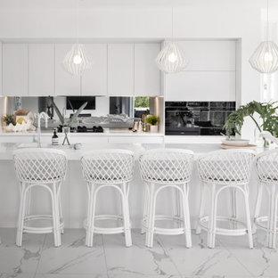 Large contemporary galley open plan kitchen in Brisbane with an undermount sink, white cabinets, quartz benchtops, black appliances, porcelain floors, with island, white floor, white benchtop, metallic splashback and mirror splashback.