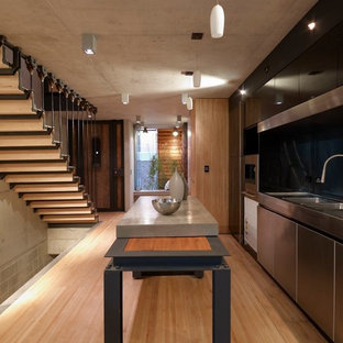 シドニーの中くらいのインダストリアルスタイルのおしゃれなキッチン (一体型シンク、フラットパネル扉のキャビネット、ステンレスキャビネット、コンクリートカウンター、黒いキッチンパネル、ガラス板のキッチンパネル、シルバーの調理設備、淡色無垢フローリング、ベージュの床、グレーのキッチンカウンター) の写真