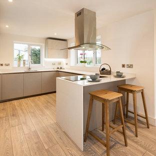 Mittelgroße Moderne Wohnküche mit Waschbecken, Glasfronten, blauen Schränken, Küchenrückwand in Rot, Küchengeräten aus Edelstahl, Laminat, grauem Boden und weißer Arbeitsplatte in Devon