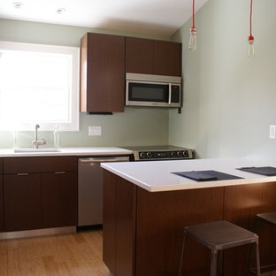 Inspiration for a small modern l-shaped eat-in kitchen in New York with an integrated sink, flat-panel cabinets, dark wood cabinets, quartz benchtops, stainless steel appliances, bamboo floors and a peninsula.