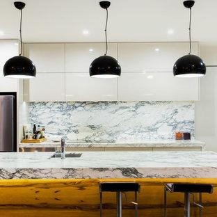 Modelo de cocina comedor en L, contemporánea, de tamaño medio, con fregadero encastrado, encimera de mármol, salpicadero de azulejos de porcelana, una isla, electrodomésticos de acero inoxidable, armarios con paneles lisos, puertas de armario blancas, suelo de cemento, salpicadero multicolor y encimeras naranjas