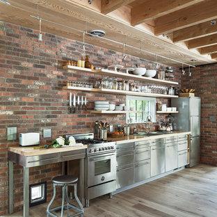 Idées déco pour une cuisine linéaire campagne avec un placard sans porte, un plan de travail en bois, une crédence en brique, un électroménager en acier inoxydable, un sol en bois clair, aucun îlot et un sol beige.