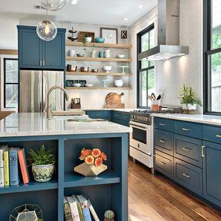 Country Küche in L-Form mit Landhausspüle, flächenbündigen Schrankfronten, blauen Schränken, Küchenrückwand in Weiß, weißen Elektrogeräten, braunem Holzboden, Kücheninsel, braunem Boden und weißer Arbeitsplatte in Austin