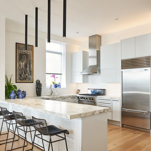Asian u-shaped kitchen in New York with an undermount sink, flat-panel cabinets, white cabinets, white splashback, stainless steel appliances, light hardwood floors, a peninsula, beige floor and beige benchtop.