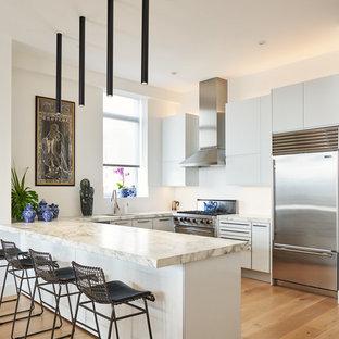 ニューヨークのアジアンスタイルのおしゃれなキッチン (アンダーカウンターシンク、フラットパネル扉のキャビネット、白いキャビネット、白いキッチンパネル、シルバーの調理設備の、淡色無垢フローリング、ベージュの床、ベージュのキッチンカウンター) の写真