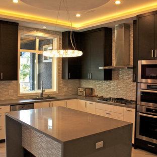 バンクーバーの中サイズのエクレクティックスタイルのおしゃれなキッチン (ダブルシンク、フラットパネル扉のキャビネット、黒いキャビネット、ラミネートカウンター、メタリックのキッチンパネル、ボーダータイルのキッチンパネル、シルバーの調理設備、大理石の床、ベージュの床) の写真