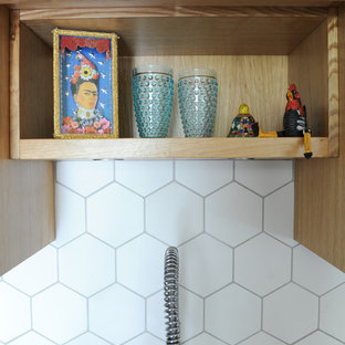 バンクーバーの小さいエクレクティックスタイルのおしゃれなキッチン (ドロップインシンク、フラットパネル扉のキャビネット、淡色木目調キャビネット、クオーツストーンカウンター、白いキッチンパネル、磁器タイルのキッチンパネル、シルバーの調理設備、磁器タイルの床、マルチカラーの床) の写真