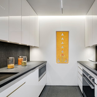 Design ideas for a small contemporary galley separate kitchen in New York with an undermount sink, flat-panel cabinets, white cabinets, marble benchtops, black splashback, marble splashback, black appliances, marble floors, black floor, black benchtop and no island.