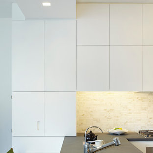 Inspiration for a small modern l-shaped eat-in kitchen in New York with an undermount sink, flat-panel cabinets, white cabinets, limestone benchtops, white splashback, stone tile splashback, stainless steel appliances, medium hardwood floors and a peninsula.