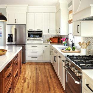 Idéer för mellanstora lantliga vitt kök, med en undermonterad diskho, skåp i shakerstil, vita skåp, bänkskiva i kvarts, grått stänkskydd, stänkskydd i porslinskakel, integrerade vitvaror, mellanmörkt trägolv och en köksö
