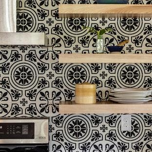 他の地域の広いトランジショナルスタイルのおしゃれなキッチン (ドロップインシンク、フラットパネル扉のキャビネット、白いキャビネット、クオーツストーンカウンター、マルチカラーのキッチンパネル、セメントタイルのキッチンパネル、シルバーの調理設備、セラミックタイルの床、マルチカラーの床、グレーのキッチンカウンター) の写真