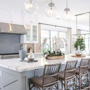 オレンジカウンティのビーチスタイルのおしゃれなアイランドキッチン (大理石カウンター、グレーのキッチンパネル、インセット扉のキャビネット、白いキャビネット、サブウェイタイルのキッチンパネル、シルバーの調理設備の、濃色無垢フローリング) の写真