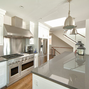 Mid-sized beach style eat-in kitchen inspiration - Eat-in kitchen - mid-sized beach style l-shaped medium tone wood floor and beige floor eat-in kitchen idea in Orange County with shaker cabinets, white cabinets, gray backsplash, stainless steel appliances, quartzite countertops, marble backsplash and an island