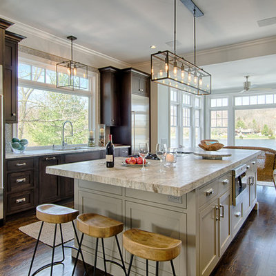 Inspiration for a large transitional u-shaped dark wood floor kitchen remodel in New York with a single-bowl sink, shaker cabinets, gray cabinets, quartzite countertops, gray backsplash, glass tile backsplash, stainless steel appliances and two islands