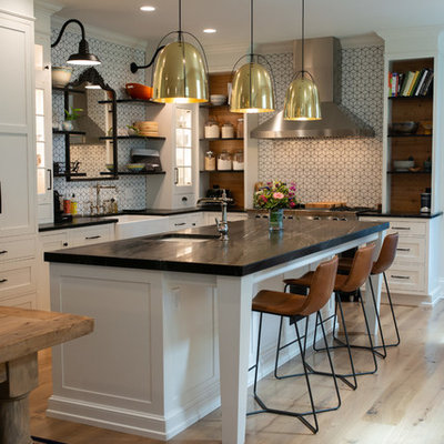 Kitchen - transitional l-shaped light wood floor and beige floor kitchen idea in Philadelphia with soapstone countertops, black countertops, a farmhouse sink, recessed-panel cabinets, white cabinets, white backsplash, mosaic tile backsplash and an island