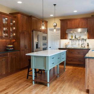 Idéer för amerikanska u-kök, med skåp i shakerstil, skåp i mörkt trä, vitt stänkskydd, stänkskydd i tunnelbanekakel och rostfria vitvaror