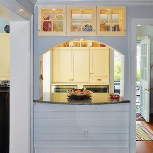 Immagine di una grande cucina costiera con ante in stile shaker, ante gialle, top in granito, pavimento in legno massello medio, pavimento marrone e top grigio