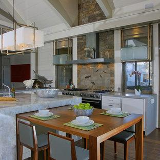 Einzeilige, Große Moderne Wohnküche mit Rückwand aus Steinfliesen, weißen Schränken, flächenbündigen Schrankfronten, Onyx-Arbeitsplatte, Küchenrückwand in Braun, Küchengeräten aus Edelstahl, dunklem Holzboden, Kücheninsel, braunem Boden und grauer Arbeitsplatte in Boston