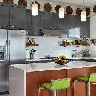 Exemple d'une cuisine tendance en L avec un évier encastré, un placard à porte plane, des portes de placard grises, une crédence blanche et un électroménager en acier inoxydable.