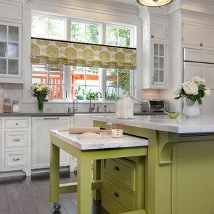 Große Klassische Küche mit Kassettenfronten, Kücheninsel, Küchenrückwand in Weiß, Rückwand aus Metrofliesen, dunklem Holzboden, weißen Schränken, Marmor-Arbeitsplatte und Elektrogeräten mit Frontblende in San Diego