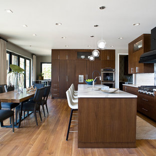 Photo of a contemporary kitchen/diner in Other with flat-panel cabinets, dark wood cabinets, multi-coloured splashback, integrated appliances, medium hardwood flooring and an island.