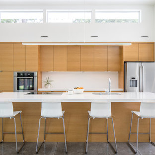 Inspiration for a mid-sized modern galley concrete floor and gray floor open concept kitchen remodel in Seattle with flat-panel cabinets, white backsplash, stainless steel appliances, an island, an undermount sink and medium tone wood cabinets