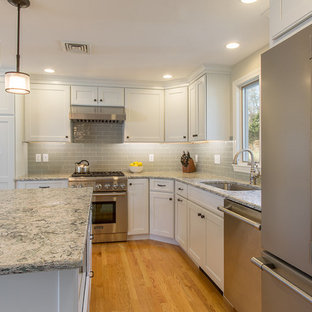 Mid-sized transitional eat-in kitchen ideas - Example of a mid-sized transitional l-shaped medium tone wood floor eat-in kitchen design in Boston with an undermount sink, recessed-panel cabinets, white cabinets, quartz countertops, green backsplash, ceramic backsplash, stainless steel appliances and an island
