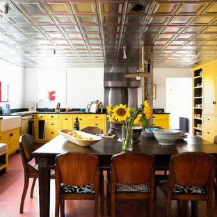 Farmhouse eat-in kitchen remodeling - Farmhouse u-shaped red floor eat-in kitchen photo in New York with a farmhouse sink, shaker cabinets, yellow cabinets, white backsplash, stainless steel appliances and black countertops