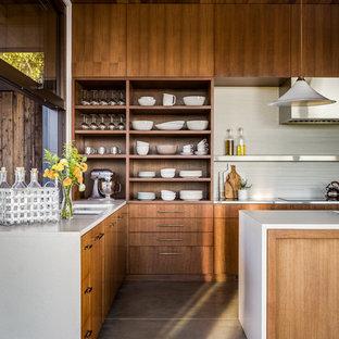 На фото: угловая кухня в восточном стиле с плоскими фасадами, темными деревянными фасадами, белым фартуком, бетонным полом, островом и серым полом