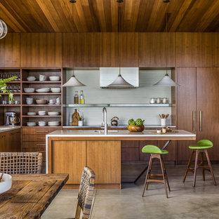 Asiatische Wohnküche in U-Form mit Unterbauwaschbecken, flächenbündigen Schrankfronten, dunklen Holzschränken, Küchenrückwand in Weiß, Küchengeräten aus Edelstahl, Betonboden, Kücheninsel und grauem Boden in San Francisco