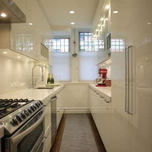 Photo of a mid-sized modern galley separate kitchen in New York with an undermount sink, flat-panel cabinets, white cabinets, stainless steel appliances, medium hardwood floors, no island, terrazzo benchtops, white splashback and stone tile splashback.