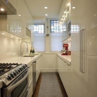 ニューヨークの中サイズのモダンスタイルのおしゃれなキッチン (アンダーカウンターシンク、フラットパネル扉のキャビネット、白いキャビネット、シルバーの調理設備の、無垢フローリング、アイランドなし、テラゾカウンター、白いキッチンパネル、石タイルのキッチンパネル) の写真