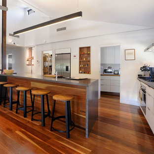 Mid-sized contemporary l-shaped kitchen in Townsville with a double-bowl sink, white cabinets, concrete benchtops, stainless steel appliances, medium hardwood floors, with island, brown floor, flat-panel cabinets and grey benchtop.