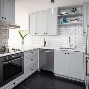Design ideas for a small contemporary u-shaped kitchen in Vancouver with an undermount sink, shaker cabinets, grey cabinets, white splashback, subway tile splashback, stainless steel appliances, black floor, white benchtop and quartz benchtops.