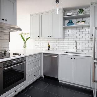 Idee per una piccola cucina ad U minimal con lavello sottopiano, ante in stile shaker, ante grigie, paraspruzzi bianco, paraspruzzi con piastrelle diamantate, elettrodomestici in acciaio inossidabile, pavimento nero, top bianco e top in quarzo composito