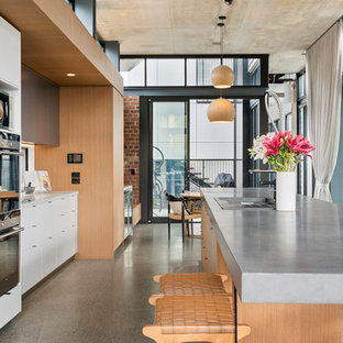 Inspiration for an expansive industrial galley open plan kitchen in Brisbane with concrete benchtops, concrete floors, with island, grey benchtop, flat-panel cabinets, white cabinets, stainless steel appliances and grey floor.