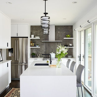 Small contemporary l-shaped separate kitchen in DC Metro with an undermount sink, flat-panel cabinets, white cabinets, quartz benchtops, grey splashback, porcelain splashback, stainless steel appliances, dark hardwood floors, with island, white benchtop and brown floor.