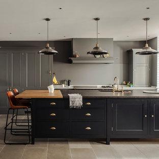 Aménagement d'une cuisine linéaire classique avec un placard avec porte à panneau encastré, des portes de placard noires et un îlot central.