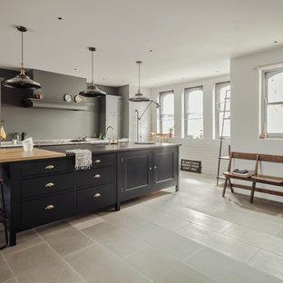 Inredning av ett klassiskt kök, med luckor med infälld panel, grå skåp, grått stänkskydd och en köksö