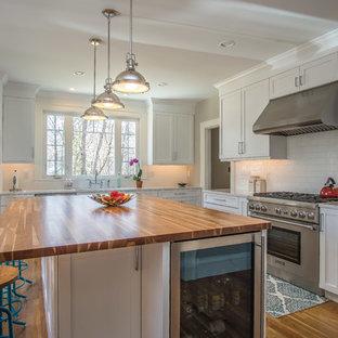 ブリッジポートの広いカントリー風おしゃれなキッチン (アンダーカウンターシンク、シェーカースタイル扉のキャビネット、白いキャビネット、クオーツストーンカウンター、白いキッチンパネル、サブウェイタイルのキッチンパネル、シルバーの調理設備、無垢フローリング、緑の床) の写真
