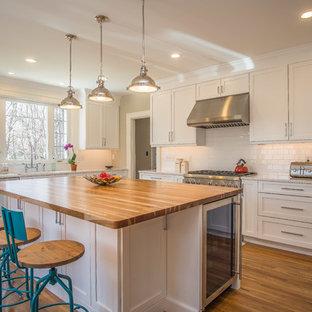 ブリッジポートの大きいカントリー風おしゃれなキッチン (アンダーカウンターシンク、シェーカースタイル扉のキャビネット、白いキャビネット、クオーツストーンカウンター、白いキッチンパネル、サブウェイタイルのキッチンパネル、シルバーの調理設備の、無垢フローリング、緑の床) の写真